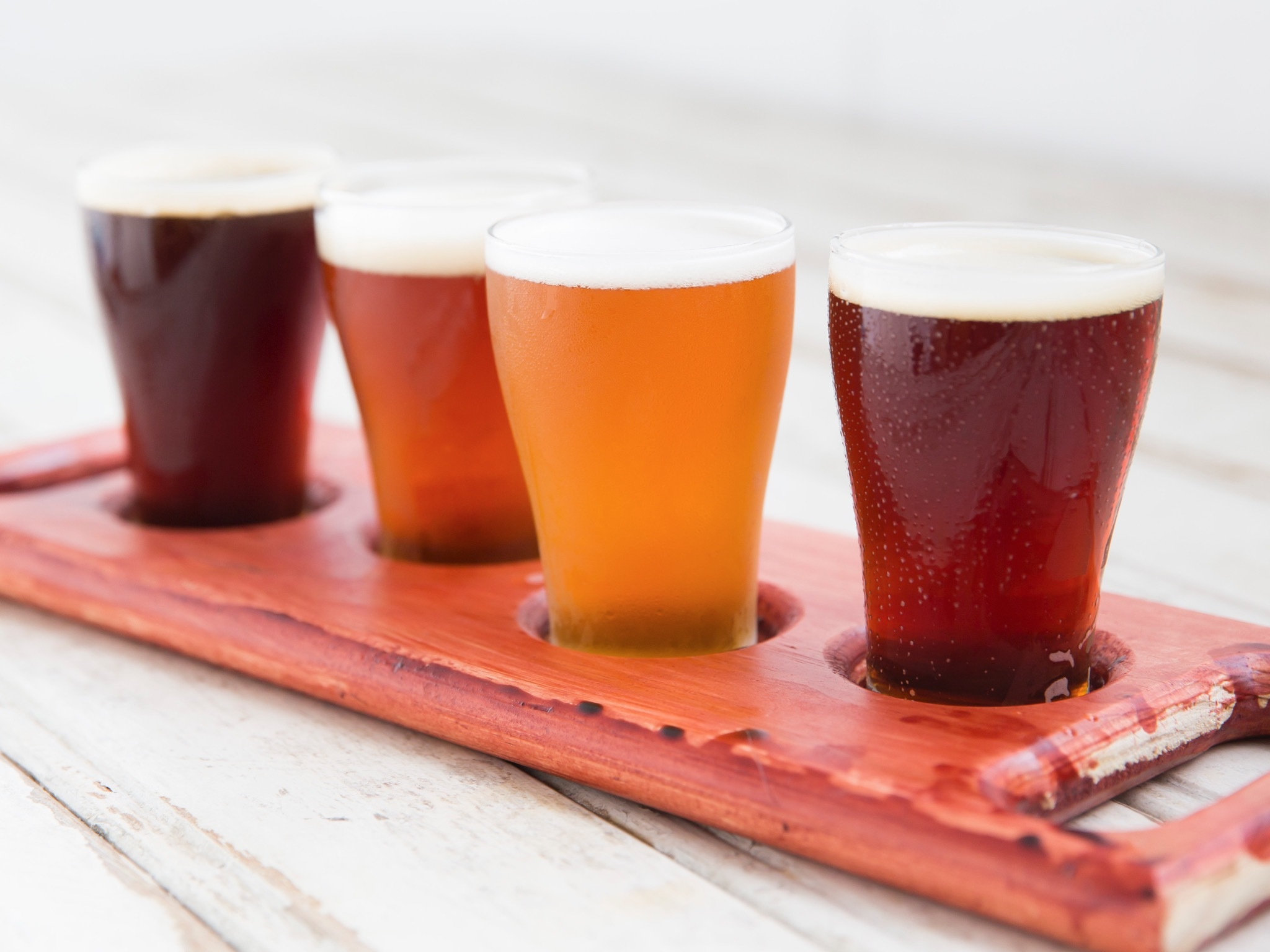 A close up shot of four beers in a wooden paddle on a table at W