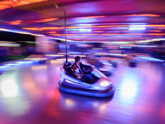 A motion shot of a bumper car driving around the arena