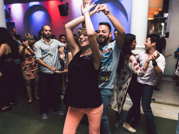 A crowd of people doing salsa dancing in a room at Establishment