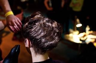 A shot of a person getting their hair blow dried at a salon.