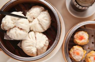 A shot of three pork buns in a bamboo steamer at Dynasty