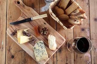 A top down shot of a cheeseboard with various cheese, a basket o