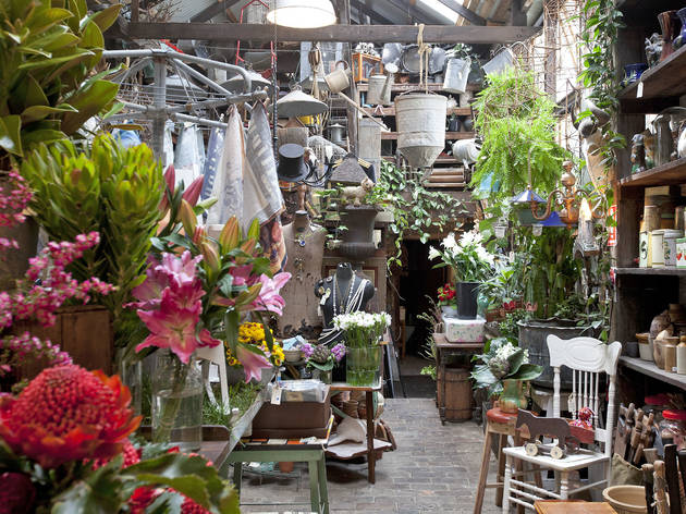 Interior shot of antique shop Seasonal Concepts with flowers, old crockery and garden tools