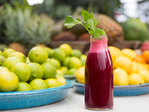 A beetroot juice surrounded by citrus fruits