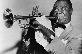 A black and white photograph of Louis Armstrong playing a trumpet
