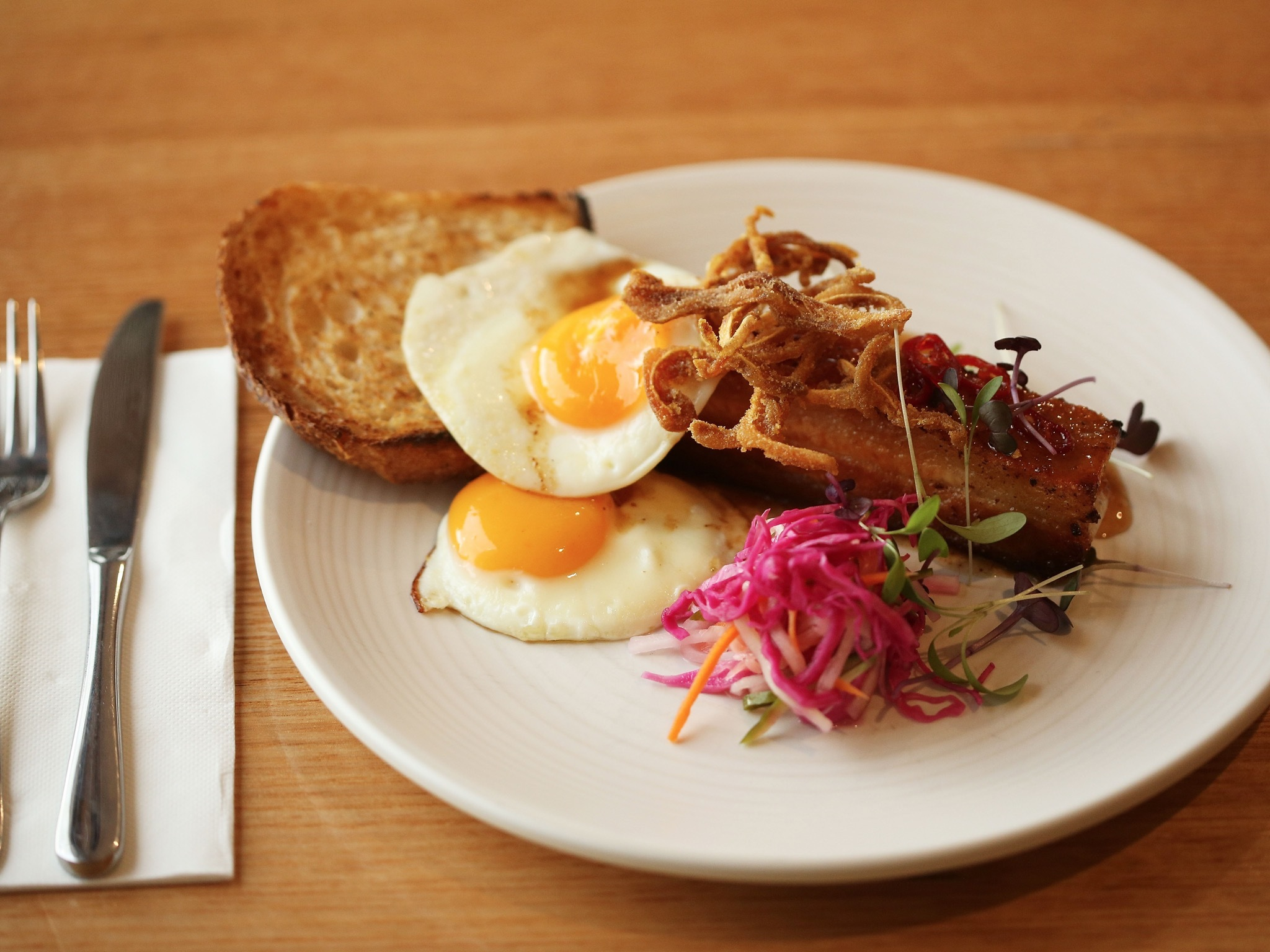 A shot of the braised pork belly, with two fried eggs and a side