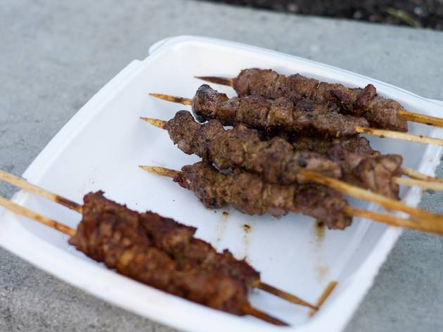 A close up shot of multiple lamb skewers in a foam take-away con