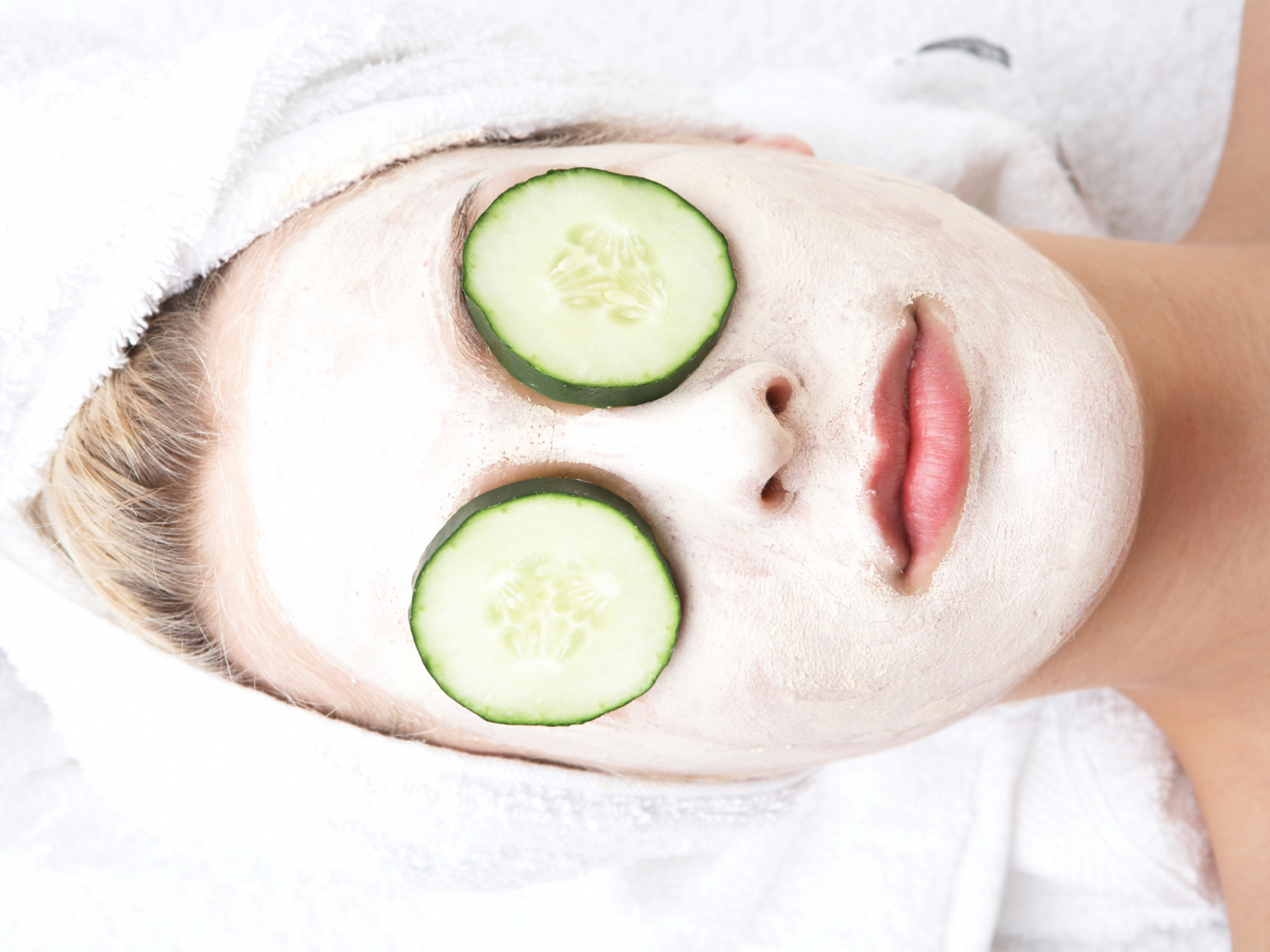 Girl witn facial mask and cucumber on her eyes