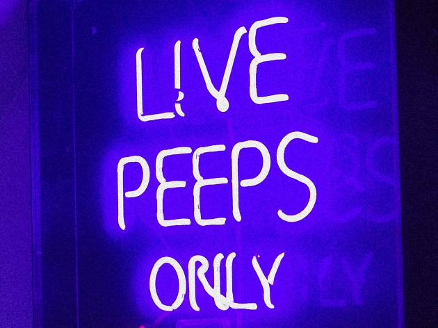 A shot of neon signs directing customers to the peep show