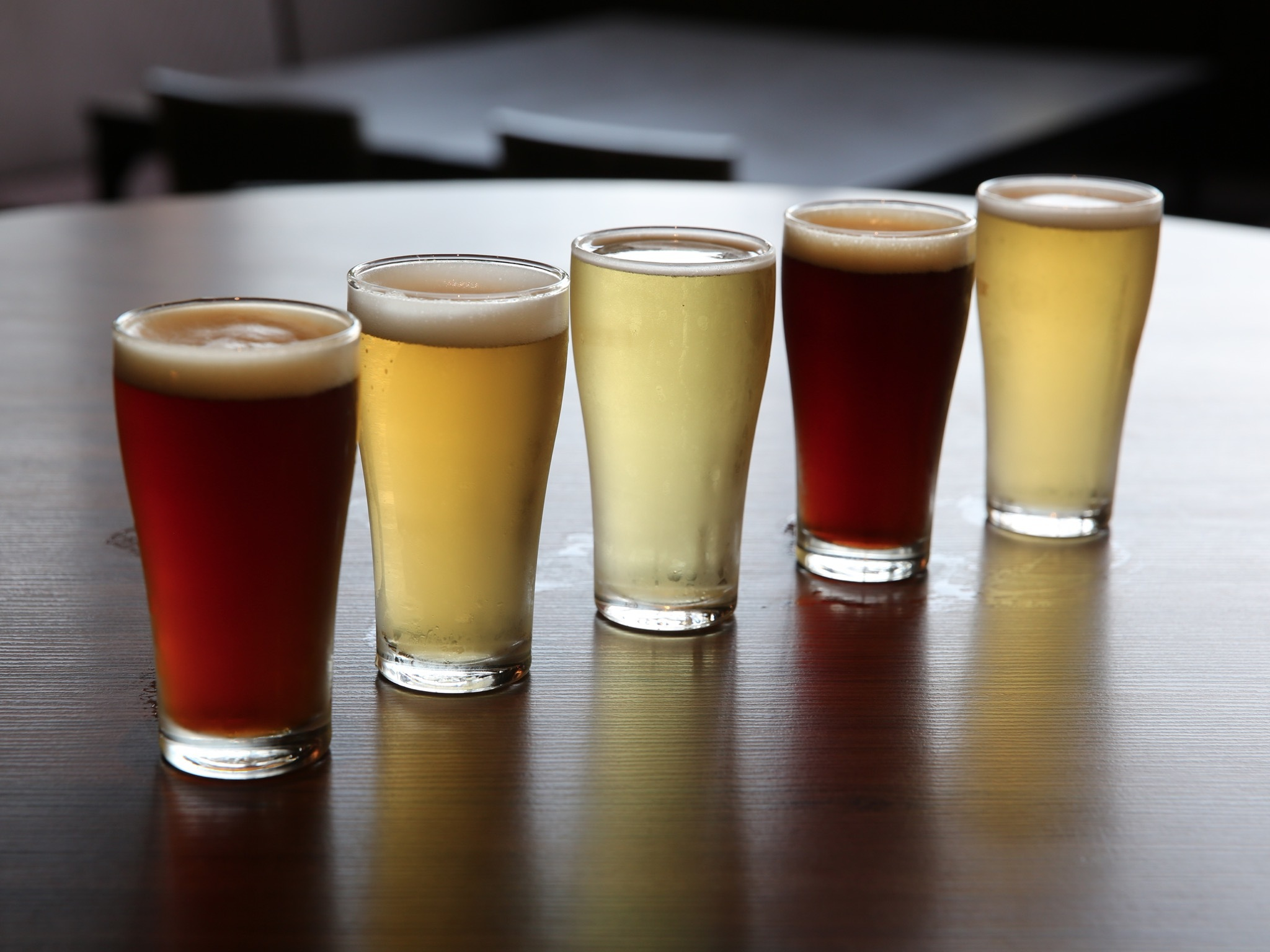 A line of five glasses of beer on a table