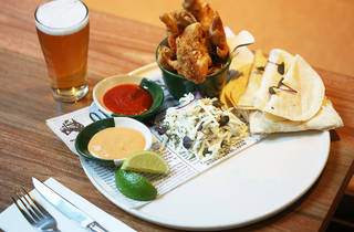 A plate for making tacos served with a beer
