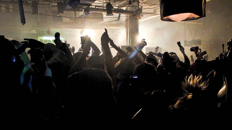 People dancing inside of a dark club