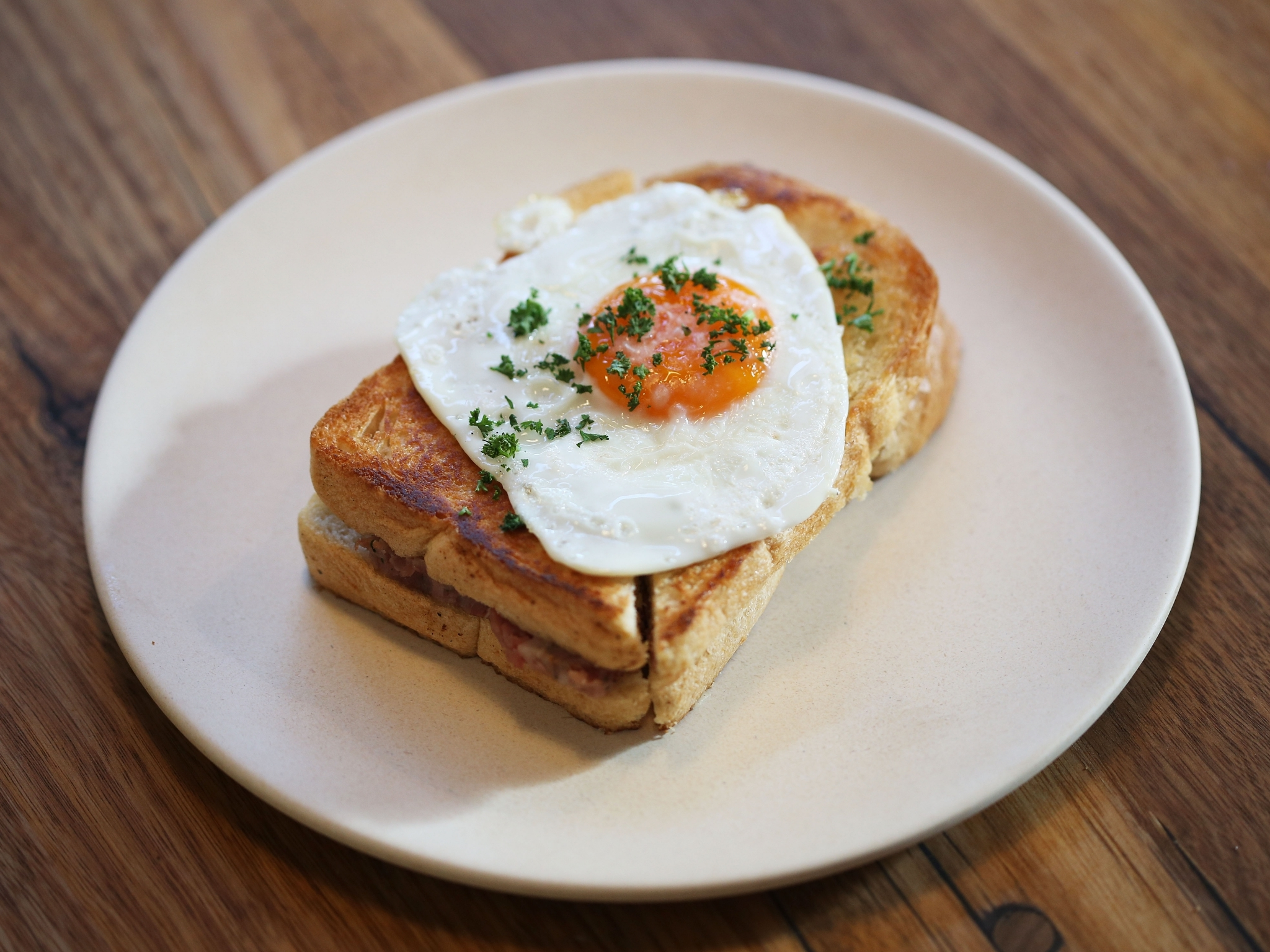A Croque Madame sandwich topped with a fried egg from the Piggery Café