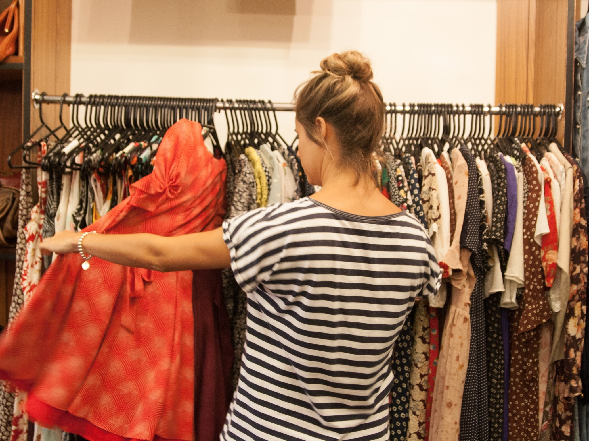A shot of a woman browsing through clothes on a rack