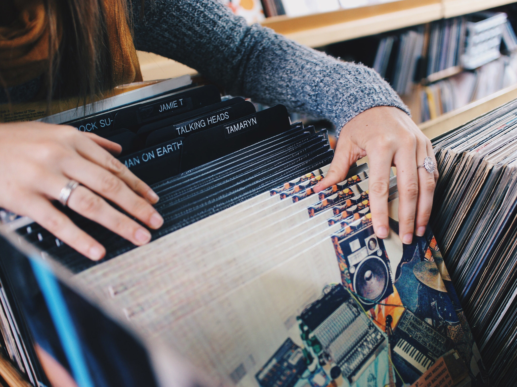 A woman searches through the vinyl collection in a record store