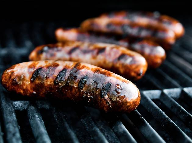 Five sausages on a barbecue grill