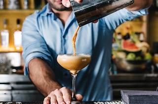 A bartender behind the bar at Barrio Cellar pouring an espresso martini