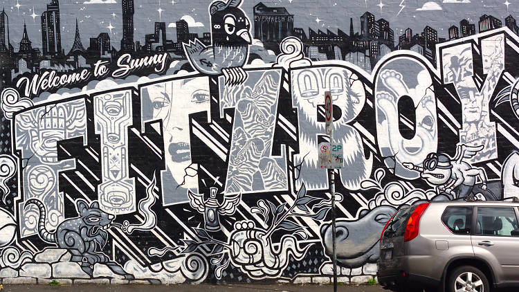 A black and grey wall mural that reads 'Welcome to Sunny Fitzroy'.