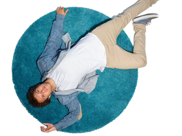 Actor Alfie Gledhill, star of Replay, lying on his back on a rug looking up at the camera.