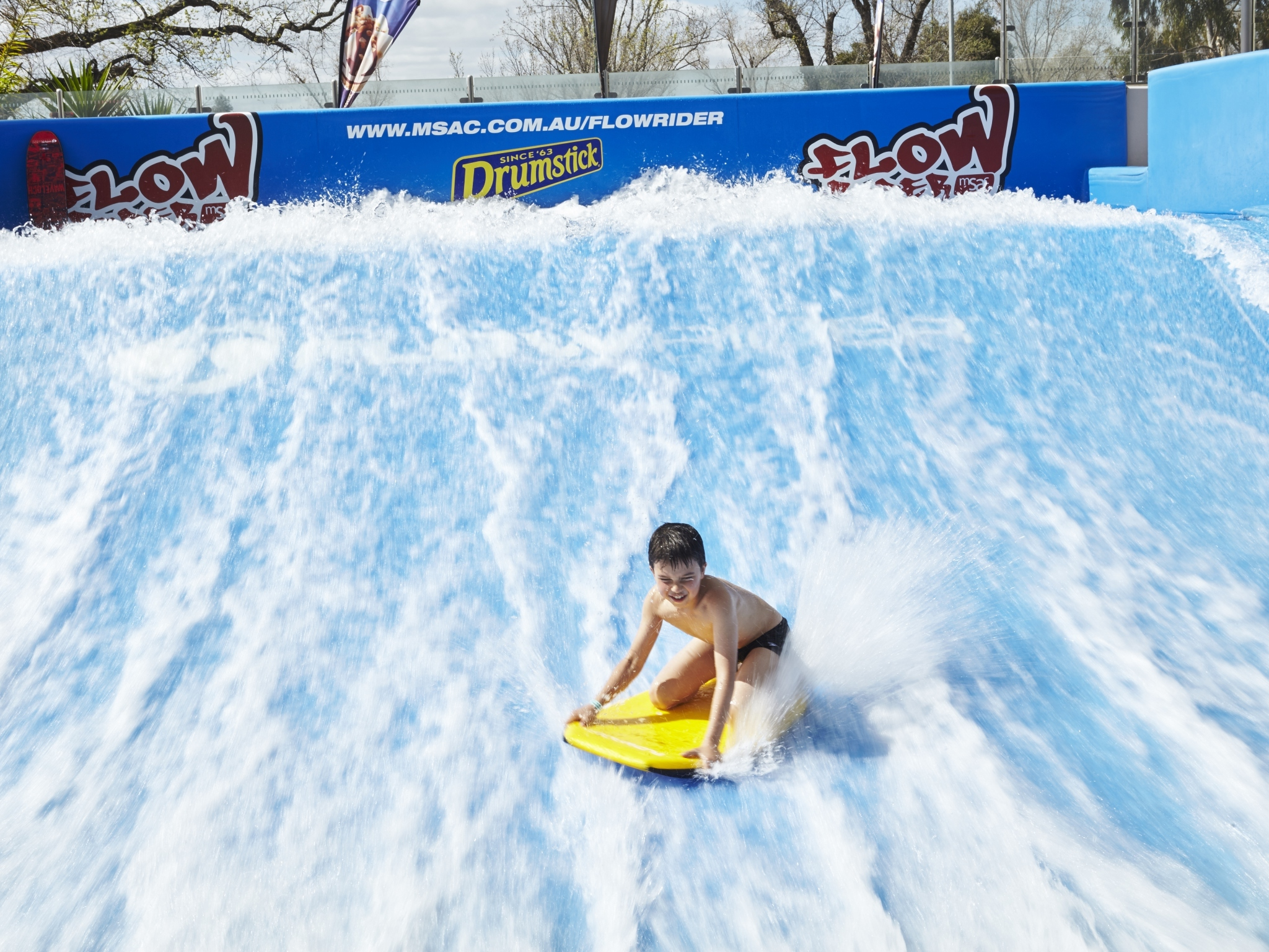 A boy rides a bodyboard on the FlowRider surfing simulator at the Melbourne Sports and Aquatic Centre (MSAC)