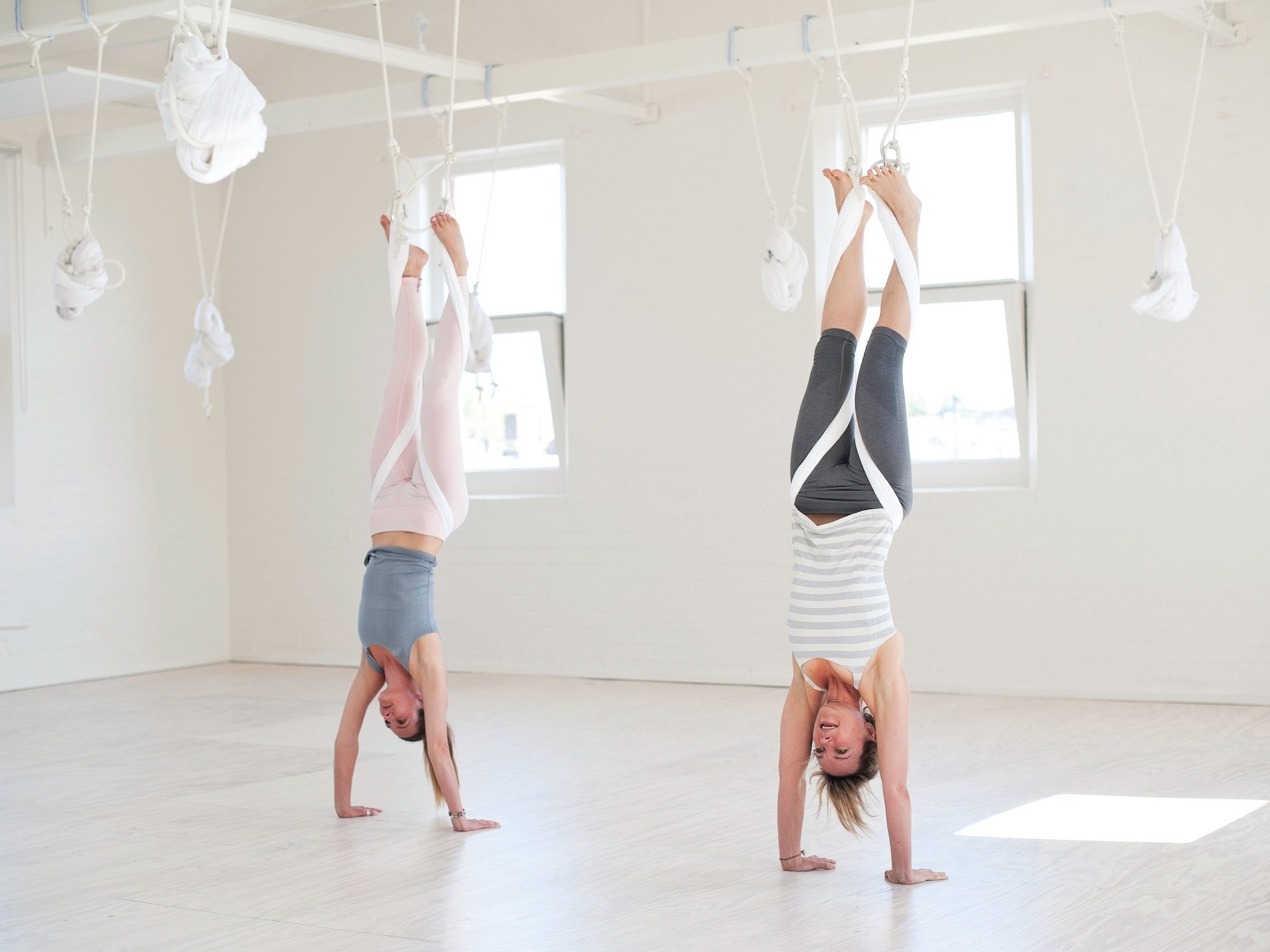 Two women practice aerial yoga at Bodyflow Yoga in Windsor