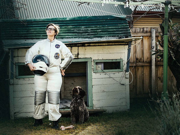 Comedian Hannah Gadsby wearing an astronaut suit, standing hands on hips and holding her helmet, in a suburban back yard