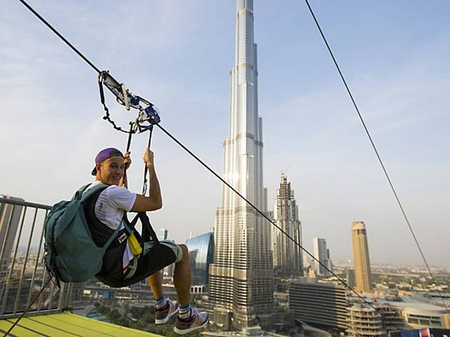 A man ziplines past the Burj Khalifa in Dubai