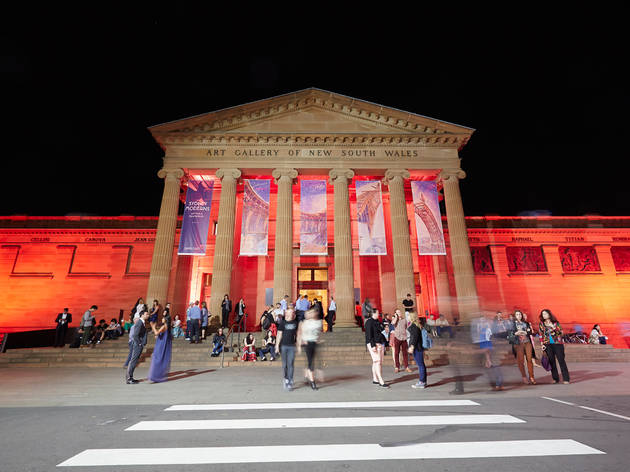 Picture of the Art Gallery of New South Wales at night from across the road, with the building lit up with red lights, and banners for Sydney Moderns exhibition hanging from the front.