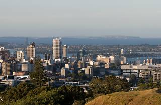 A photograph of the Auckland skyline, facing towards the city's harbour, with olive green hills in the foreground