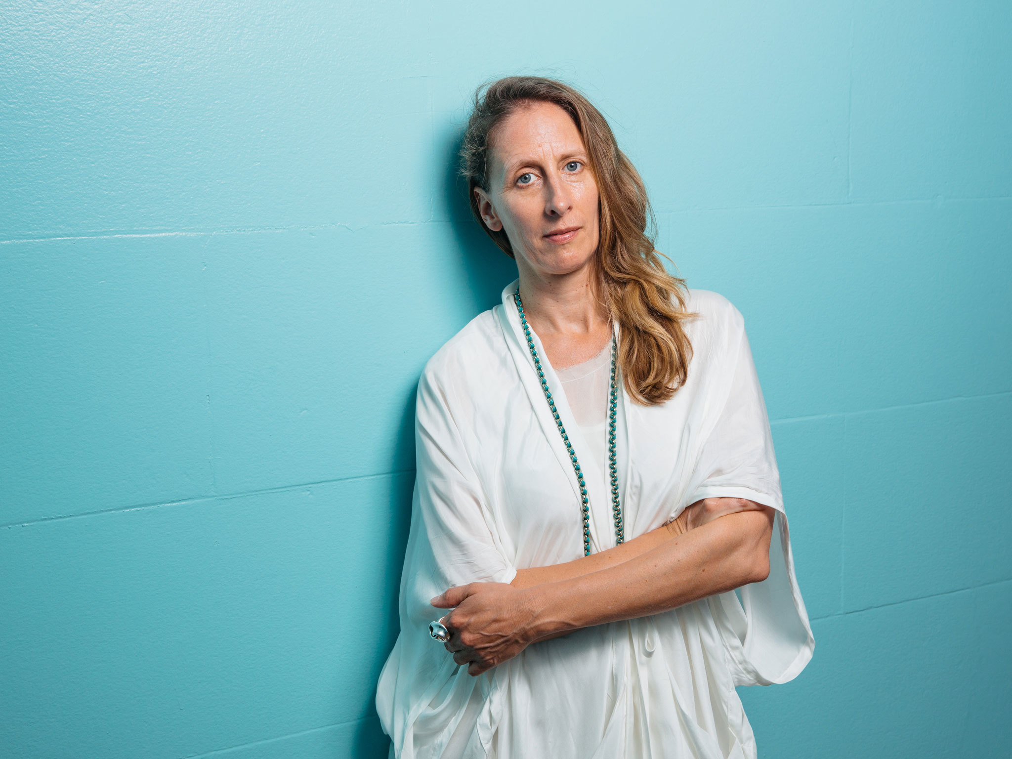 Image of Biennale of Sydney curator Stephanie Rosenthal with her hair out and wearing loose-fitting white robes, standing with her arms folded against the bright turquoise wall of Mortuary Station