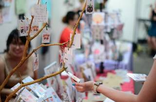 Market stall of handmade cards woman looking at card