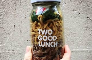 A jar filled with egg noodles and salad
