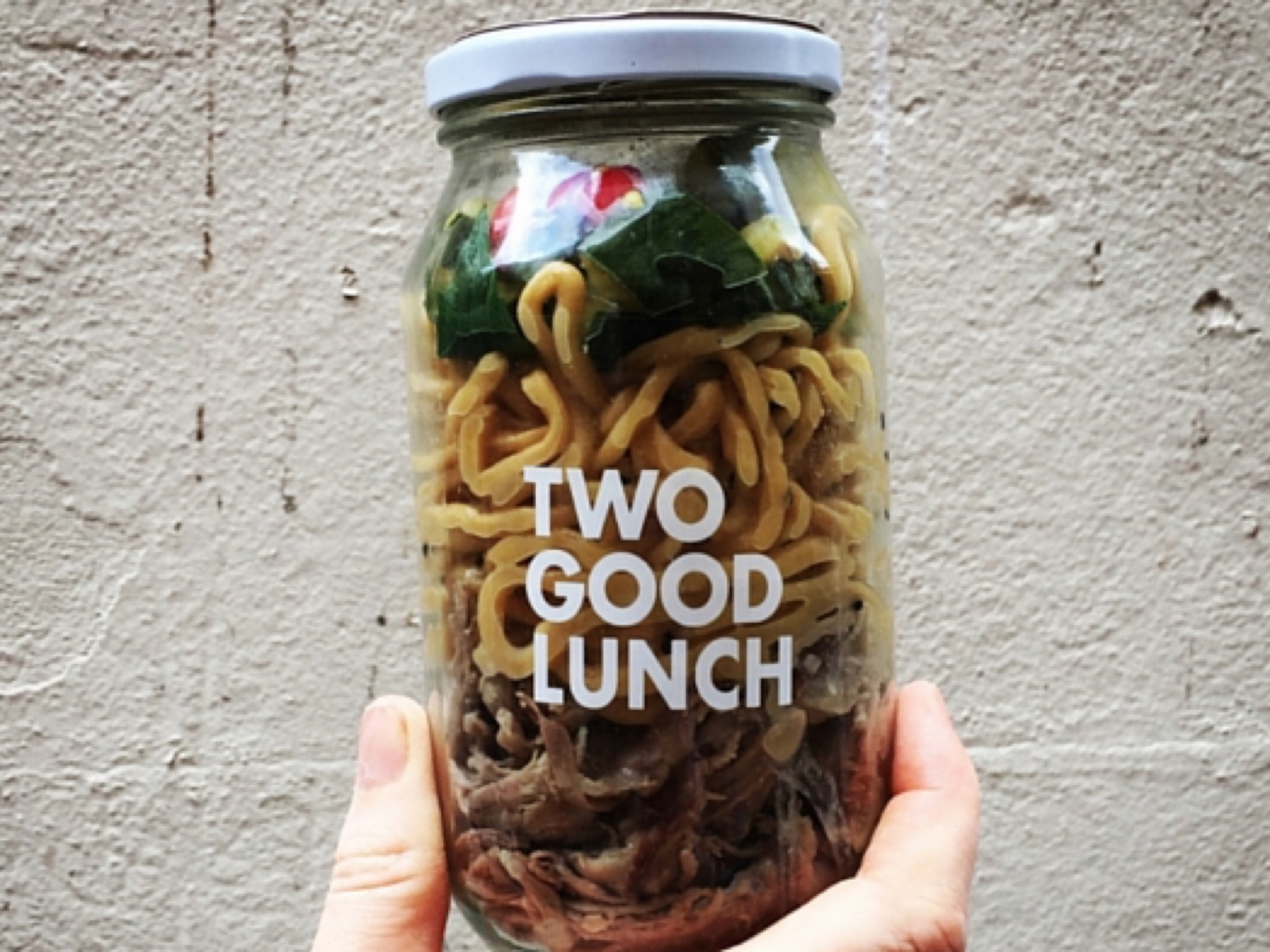 A jar filled with egg noodles and salad