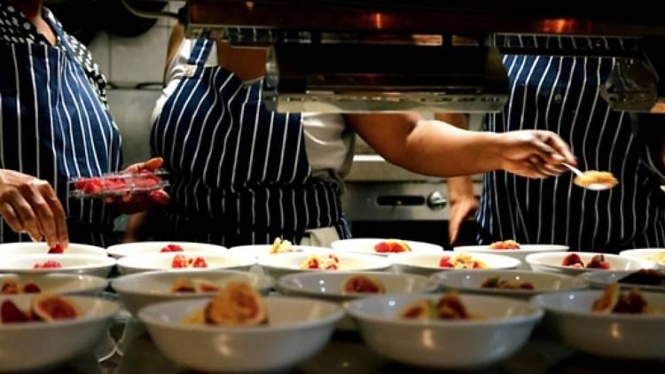 Chefs plating up dessert behind a kitchen pass