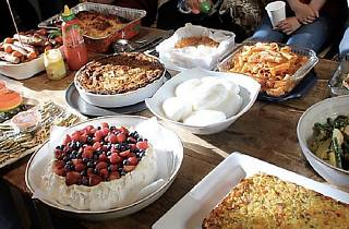 Buffet table featuring salad, pasta and pavlova