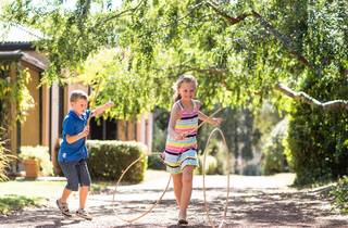 Girl and a boy play with hoops and sticks outside
