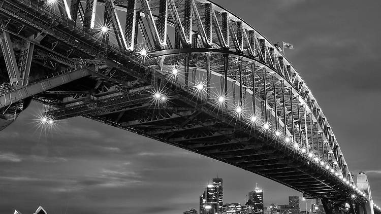 A black and white photograph of the Sydney Harbour bridge, taken at night with the lights on.