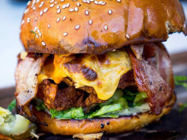 Fried chicken burger with bacon, cheese and salad