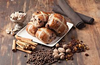 A plate of hot cross buns surrounded by spices including cinnamon, juniper berries, nutmeg as well as sultanas and raisins