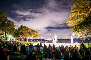A crowd of people sitting in Robertson park at twilight watching actors performing on a stage with the bay behind them.