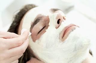 A man receives a facial treatment at a spa