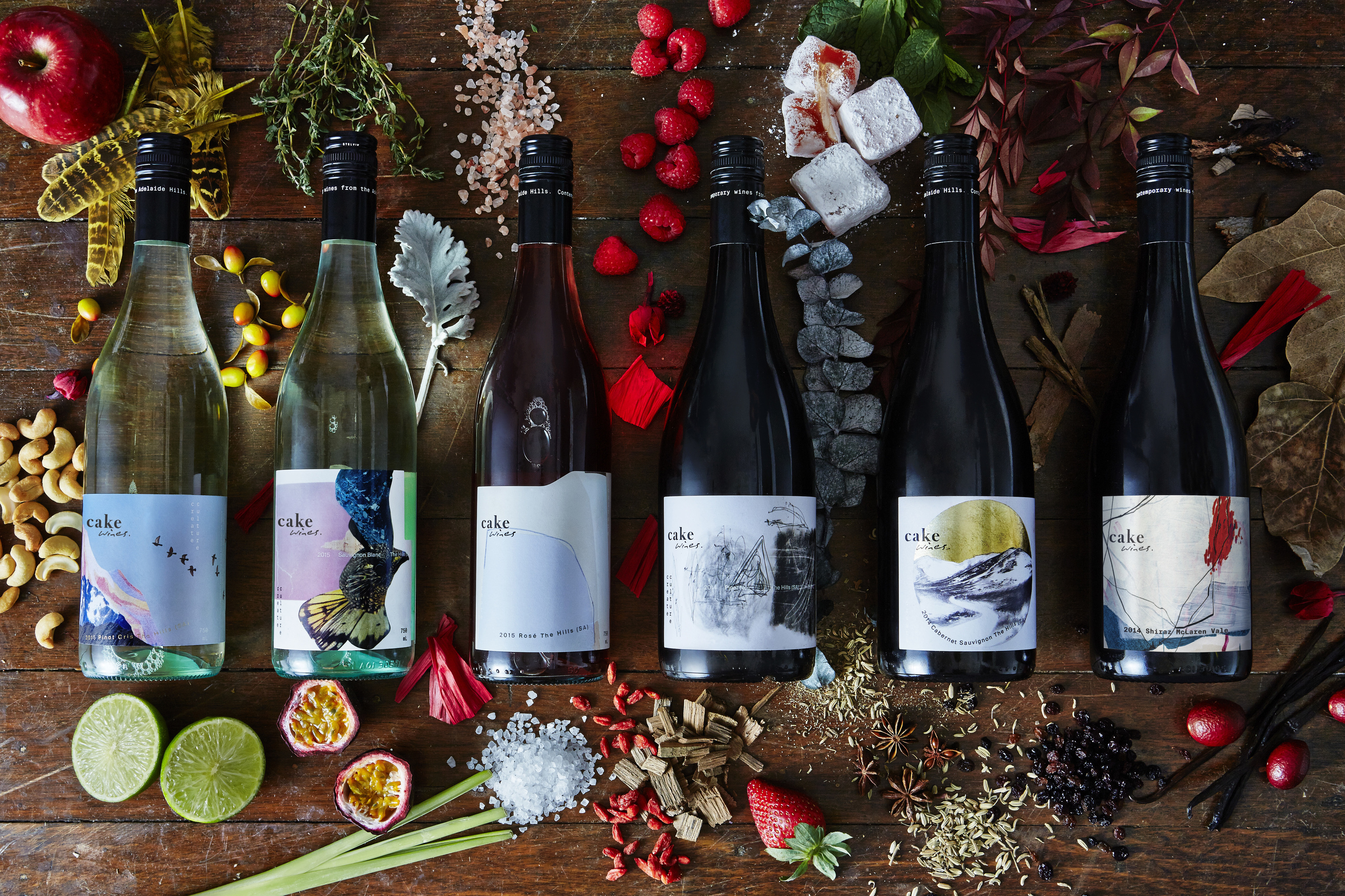 Five different wine bottles laid out on wooden table with various fruits and flowers surrounding them