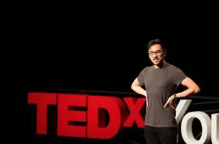 Michael Hing standing on stage at TEDxYouth 2015