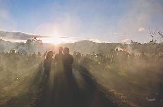 This is a misty scene of the Huon Valley in Tasmania with people standing around an sunset with a bonfire blazing in the background