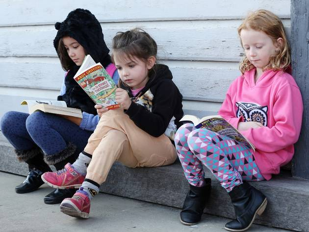 Three children reading books