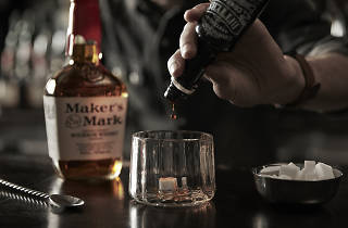 A Maker's Mark Old Fashioned cocktail being made on a bartop