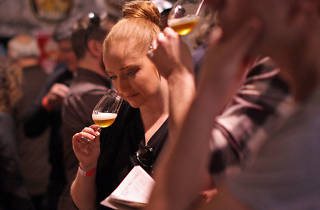 A woman sniffing a glass of craft beer