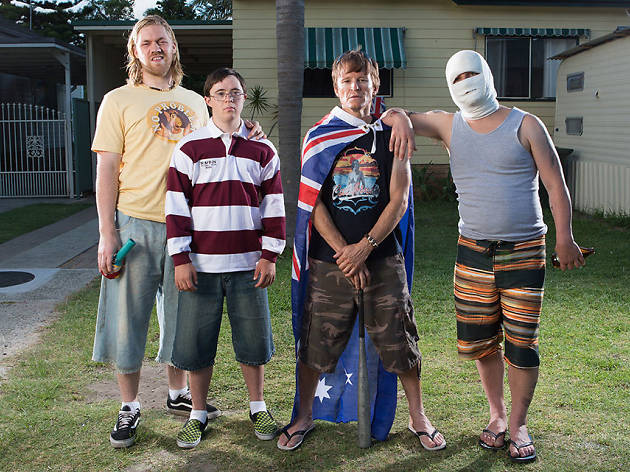 Group of boys, one wearing the Australian flag as a cape, stand outside a suburban home