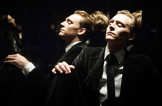 Tom Hiddleston in film High Rise, sitting in room with his reflection shown against the glass