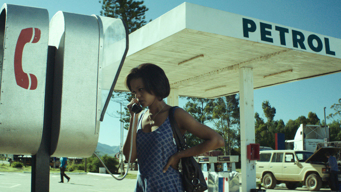 A young woman at a payphone in front of a petrol station